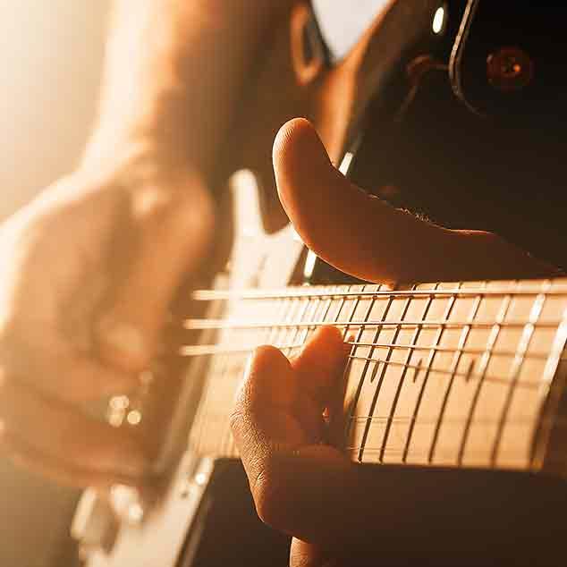 Un musicista rock che suona la chitarra elettrica ad un concerto con nebbia e luce.