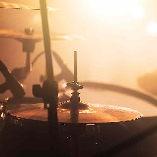 Drums on a concert stage with mist and light.