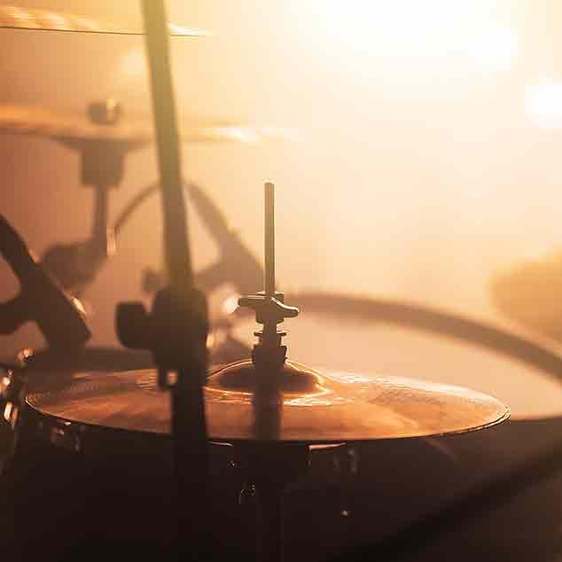 Perkusista na zadymionej oraz oświetlonej scenie.
