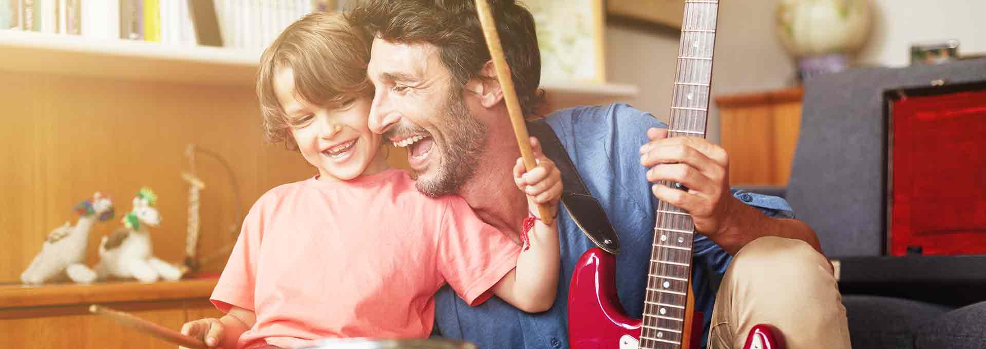 Vader met Bernafon Viron hoortoestellen, speelt gitaar met zijn vijf jaar oude zoon die op de drums speelt en ze genieten van het moment.