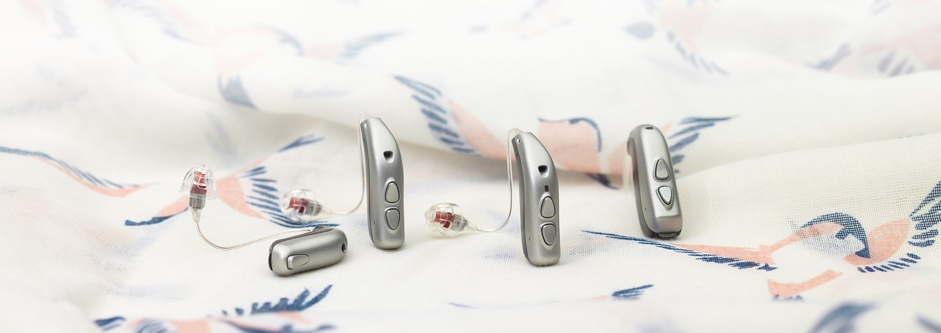 The complete Bernafon Viron hearing aid family with BTE, miniRITE, miniRITE T and miniRITE T R on a scarf with bird prints.