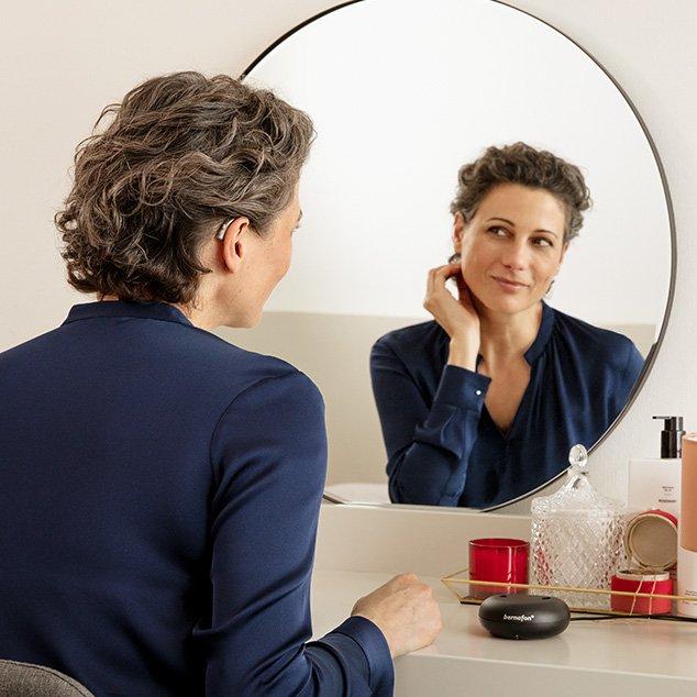 Mujer llevando audífonos recargables Bernafon Alpha sentada frente a un espejo en una mesa de maquillaje con cargador para audífonos