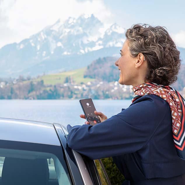 Frau trägt wiederaufladbare Bernafon Alpha Hörgeräte, steht an ihrem Auto, schaut auf einen Schweizer See und telefoniert dabei über ihr Smartphone.