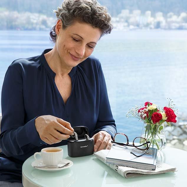 Frau sitzt an einem Tisch, im Hintergrund ein Schweizer See, sie entnimmt gerade ihre wiederaufladbaren Bernafon Alpha Hörgeräte aus der mobilen Ladestation Plus.