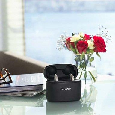 Aides auditives Bernafon Alpha rechargeables dans un chargeur portable Charger Plus sur une table en verre avec des fleurs rouges, un livre et des lunettes.