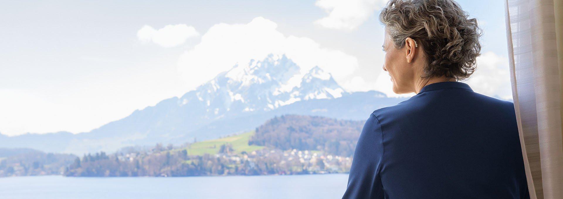 Mujer vistiendo audífonos recargables Bernafon Alpha disfruta de vistas al lago suizo y a la montaña desde la ventana del hotel