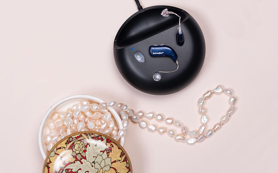 Audífonos recargables Bernafon Alpha azul medianoche en el cargador junto a un joyero y un collar de perlas blancas