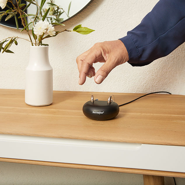 Woman removing Bernafon Alpha rechargeable hearing aids from the charger that sits on a table next to a flower vase