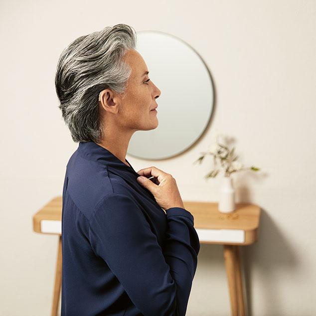 Zijprofiel van een vrouw die Bernafon Alpha oplaadbare hoortoestellen draagt en haar blouse goed doet, staand voor een tafel en een spiegel