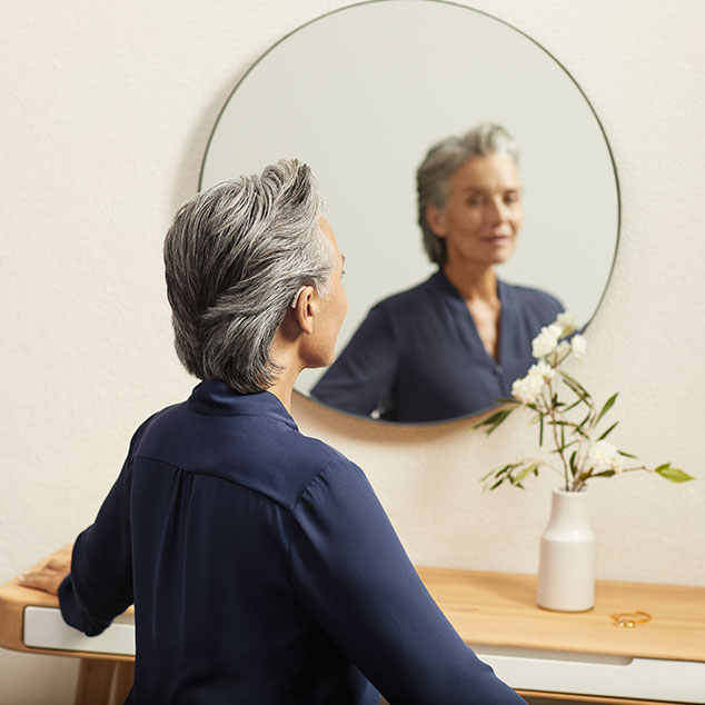 Woman wearing Bernafon Alpha rechargeable hearing aids looks into a round mirror and sits on a table with white flowers
