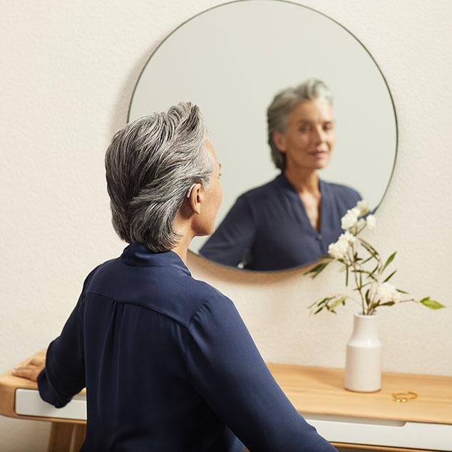Kobieta z ładowalnymi aparatami słuchowymi Bernafon Alpha patrzy w okrągłe lustro i siada przy stole z flakonem białych kwiatów
