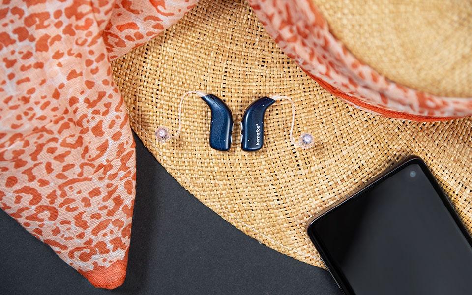 Des appareils auditifs rechargeables Bernafon Alpha bleu nuit placés à côté d'un smartphone sur un chapeau de paille avec un foulard imprimé animal