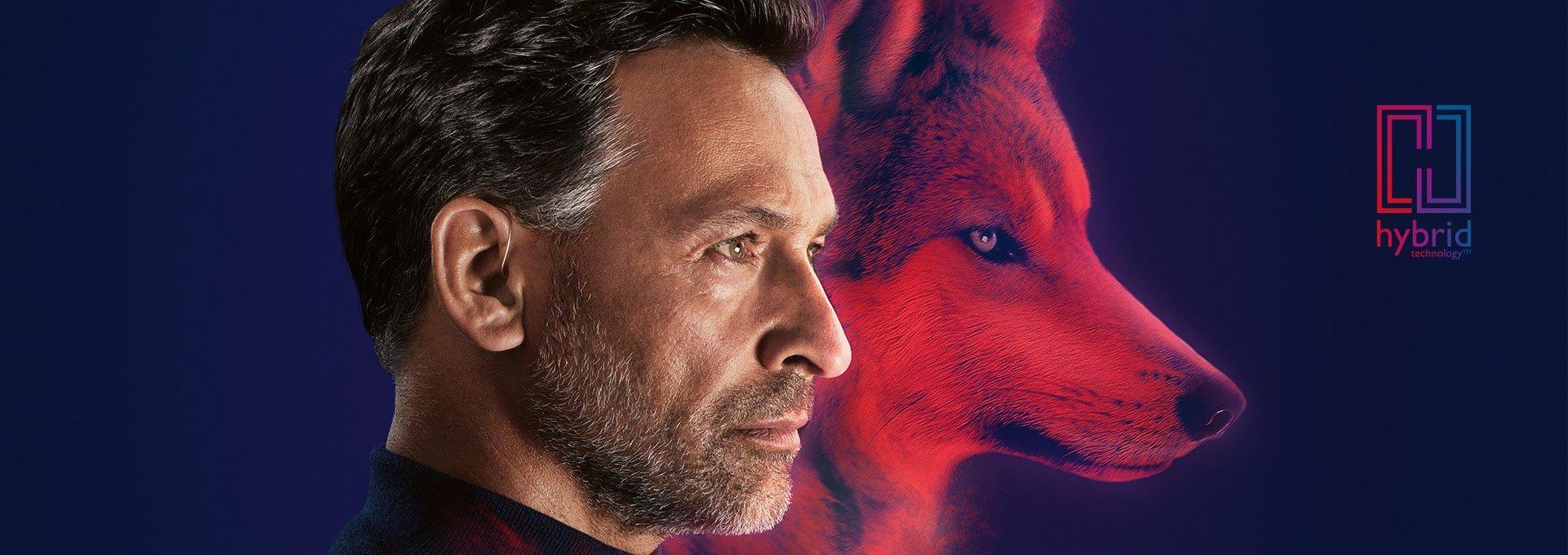 Mężczyzna o wyrazistym profilu, noszący ładowalne aparaty słuchowe Bernafon Alpha wpisany w wizerunek wilka i logo technologii hybrydowej