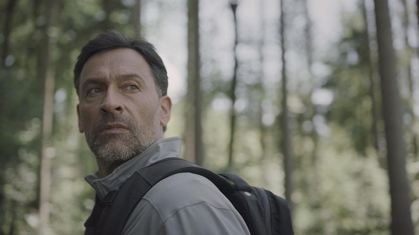 Film de présentation de l'appareil auditif rechargeable Bernafon Alpha montrant un loup et un homme s'entendant dans la forêt avant de se rencontrer.
