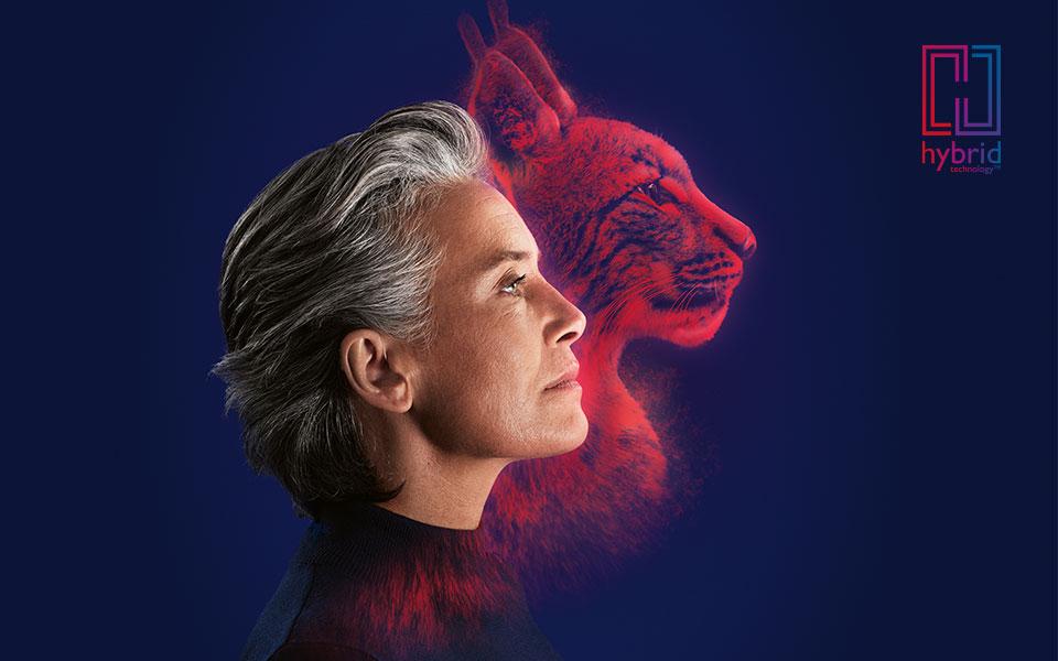 Femme au profil latéral fort portant des appareils auditifs rechargeables Alpha, une silhouette de lynx et le logo de la technologie hybride
