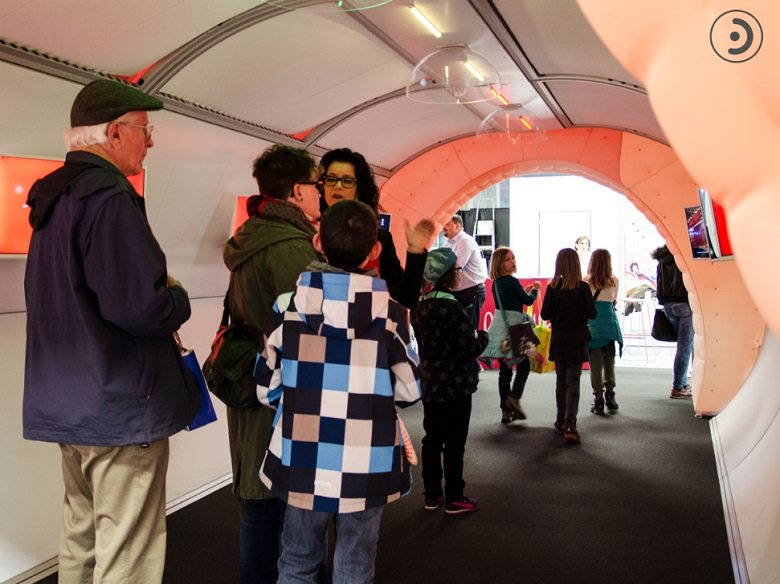 Adults and children walking through the Bernafon tunnel at an annual fair. Hearing aid expert answers questions about hearing.