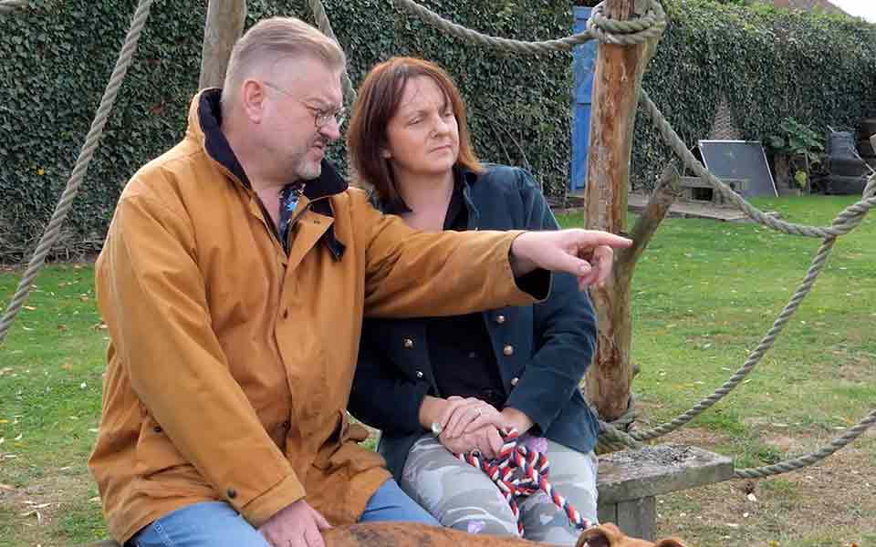 Middle-aged couple with dog sitting on park bench. He's wearing Bernafon Zerena hearing aids, pointing to something he hears.