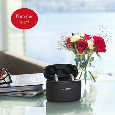 Genopladelige Bernafon Alpha høreapparater i den transportable oplader Charger Plus på et glasbord med røde blomster, en bog og et par briller