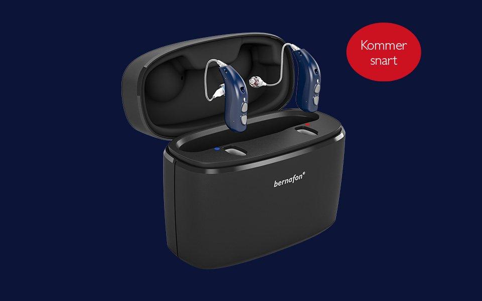 Genopladelige Bernafon Alpha høreapparater i midnight blue placeret i den transportable oplader Charger Plus, der har åbent låg