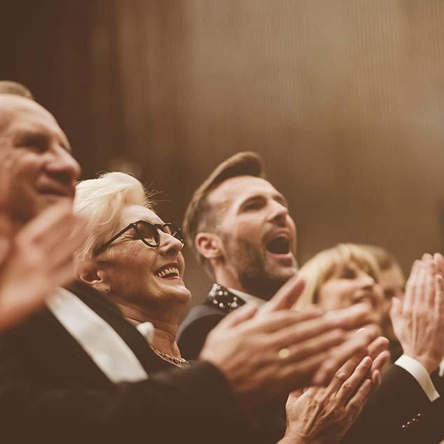 Audiencia bien vestida en un teatro con una mujer con audífonos Bernafon Alpha, aplaude el concierto de música clásica