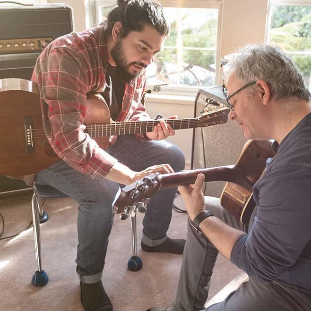Älterer Mann trägt wiederaufladbare Bernafon Alpha Hörgeräte und nimmt bei einem jüngeren Lehrer Gitarrenunterricht.
