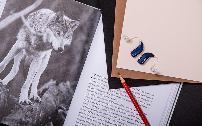 Audífonos recargables Bernafon Alpha azul medianoche colocados sobre un libro con la imagen de un lobo junto a un lápiz rojo