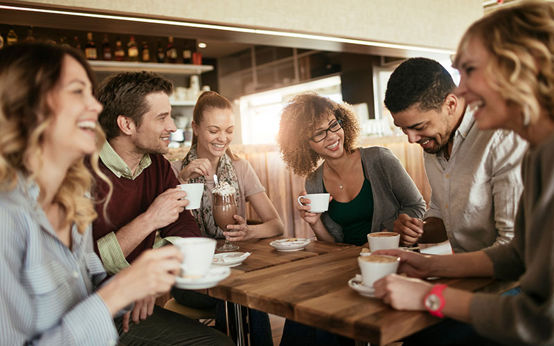 Vrolijke mensen die rond een tafel zitten en koffie drinken om de luistersituatie van Bernafon Alpha oplaadbare hoortoestellen te laten zien
