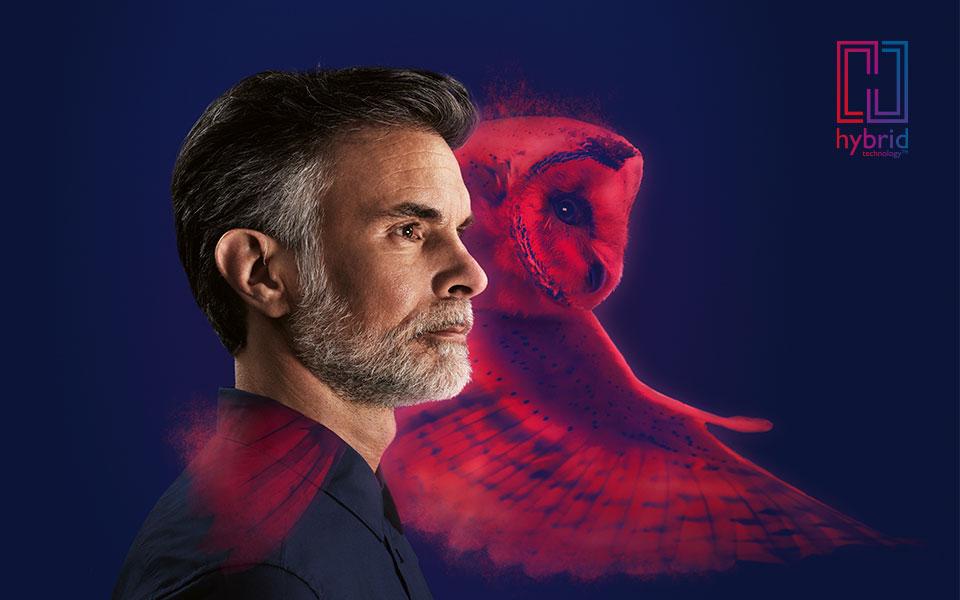 Homme au profil latéral fort portant des appareils auditifs rechargeables Alpha par le dessin d'un hibou et le logo de la technologie hybride