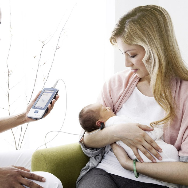 A mother holding her baby while doctor is performing a screening with a MAICO easyScreen