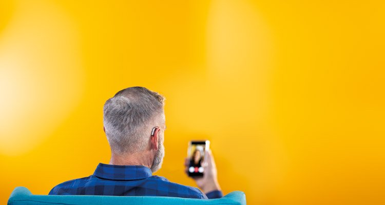 Middle-aged man using his smartphone and his Philips HearLink hearing aids to connect to friends by making a video call.