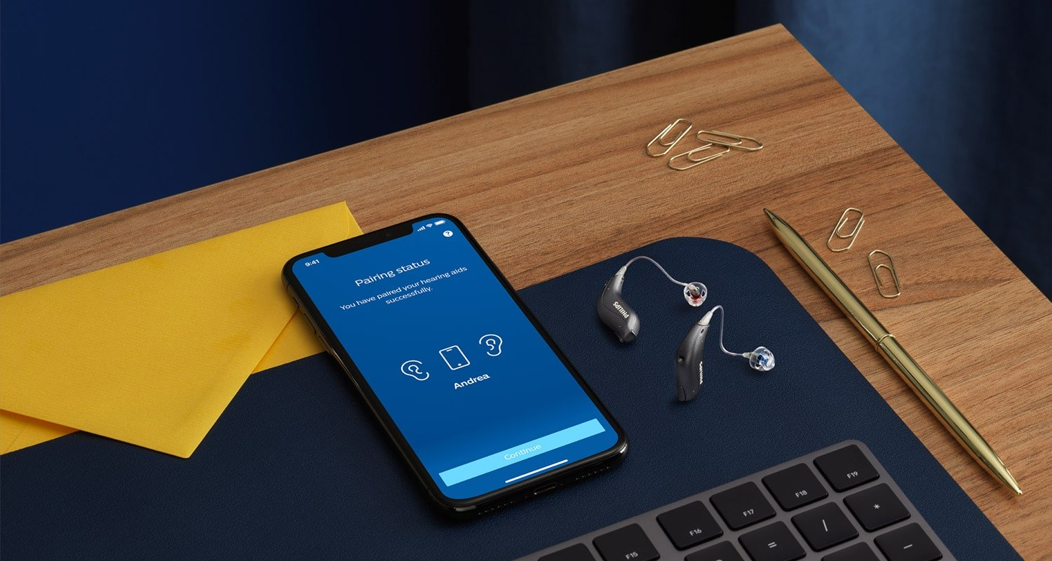 Philips HearLink miniRITE hearing aids next to a smartphone with the Philips HearLink app open.