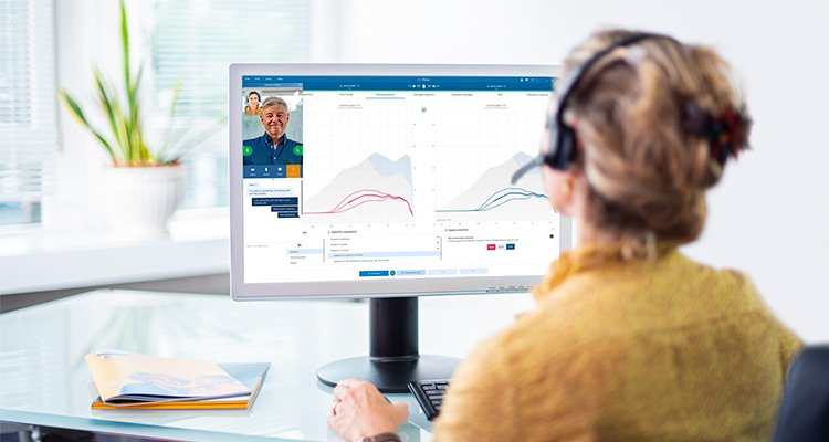 Audiologist sitting in front of computer using the Fitting Assistant feature in Philips HearSuite