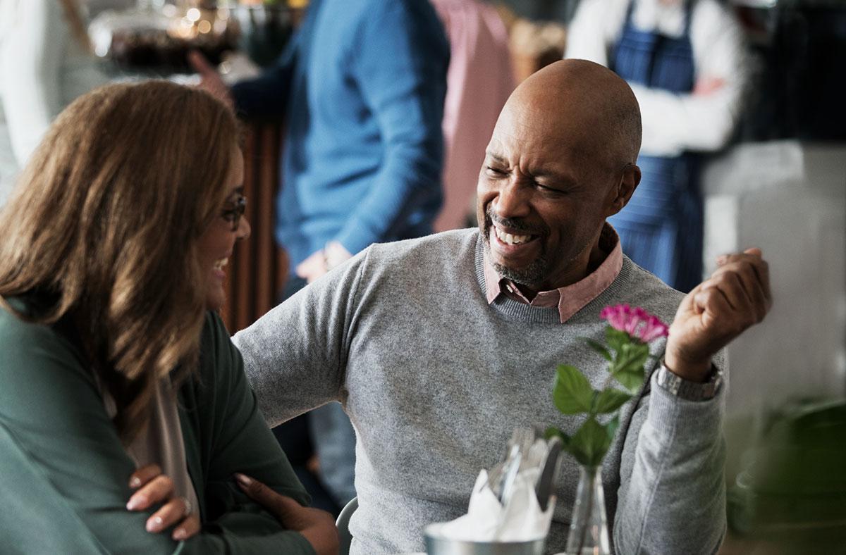 homme souriant en conversation avec femme à lunettes