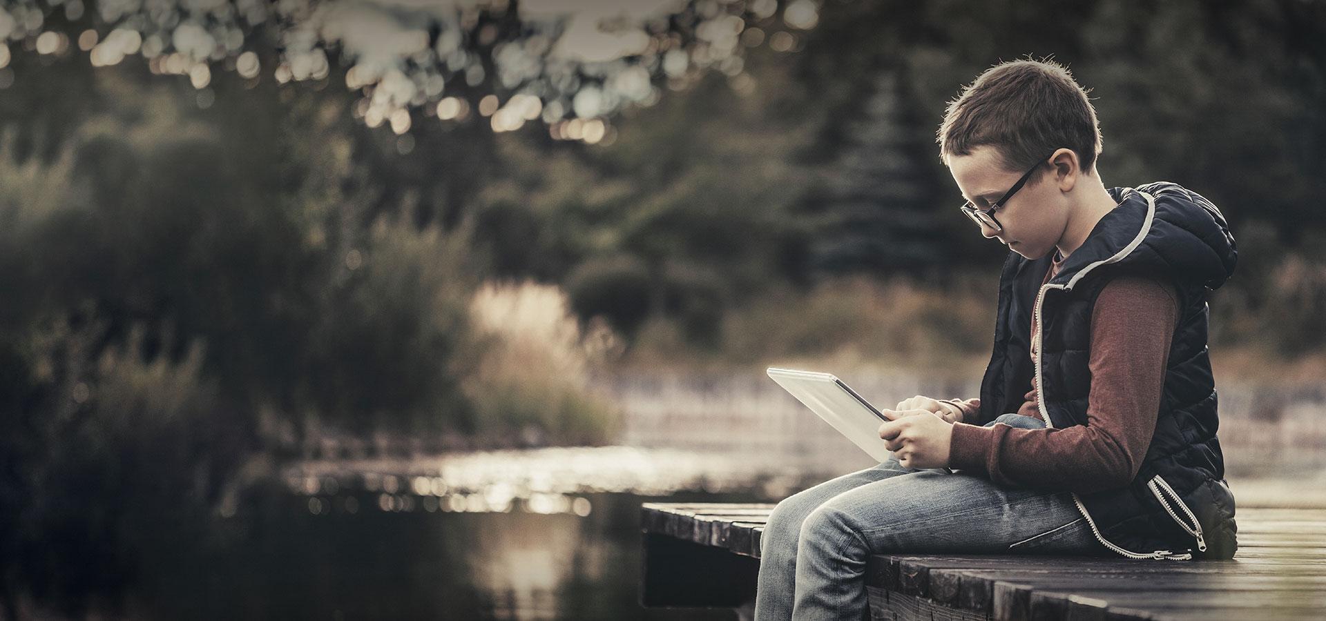 enfant assis au bord de l'eau avec une tablette numérique au bord de l'eau