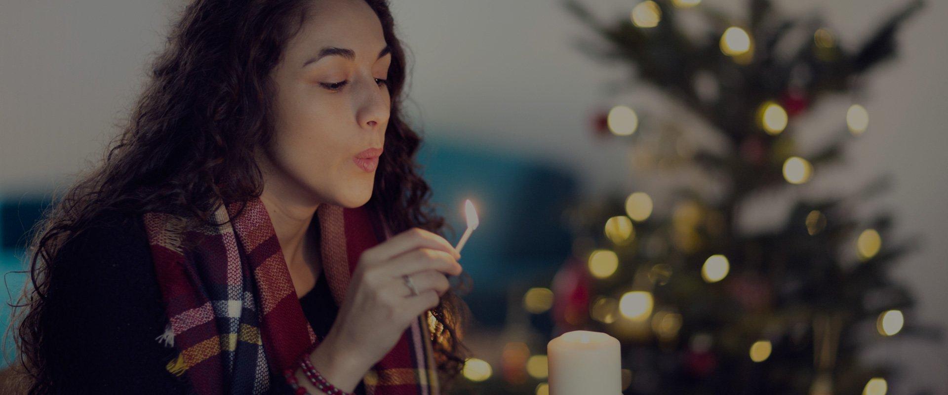 jeune femme brune aux cheveux bouclés souffle une allumette sur une bougie près d'un sapin de noel