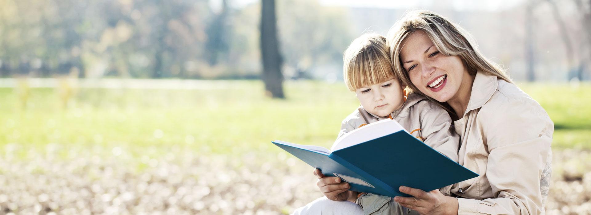 Mère racontant une histoire à son enfant dans un parc ensoleillé