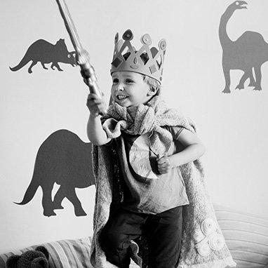 enfant déguisé en roi avec épée et couronne en train de jouer
