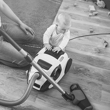 bébé s'amusant avec un aspirateur