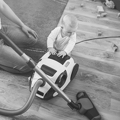 Infant standing against a vacuum cleaner