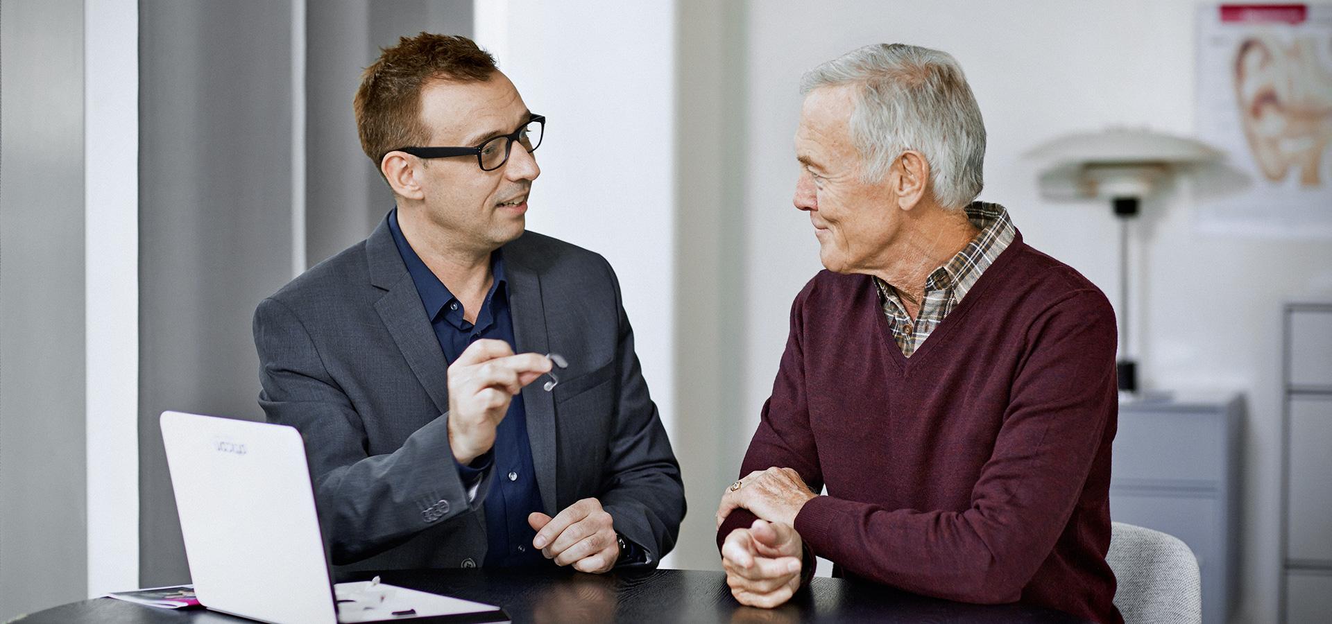 un audioprothésiste et son patient parlant des appareils auditifs