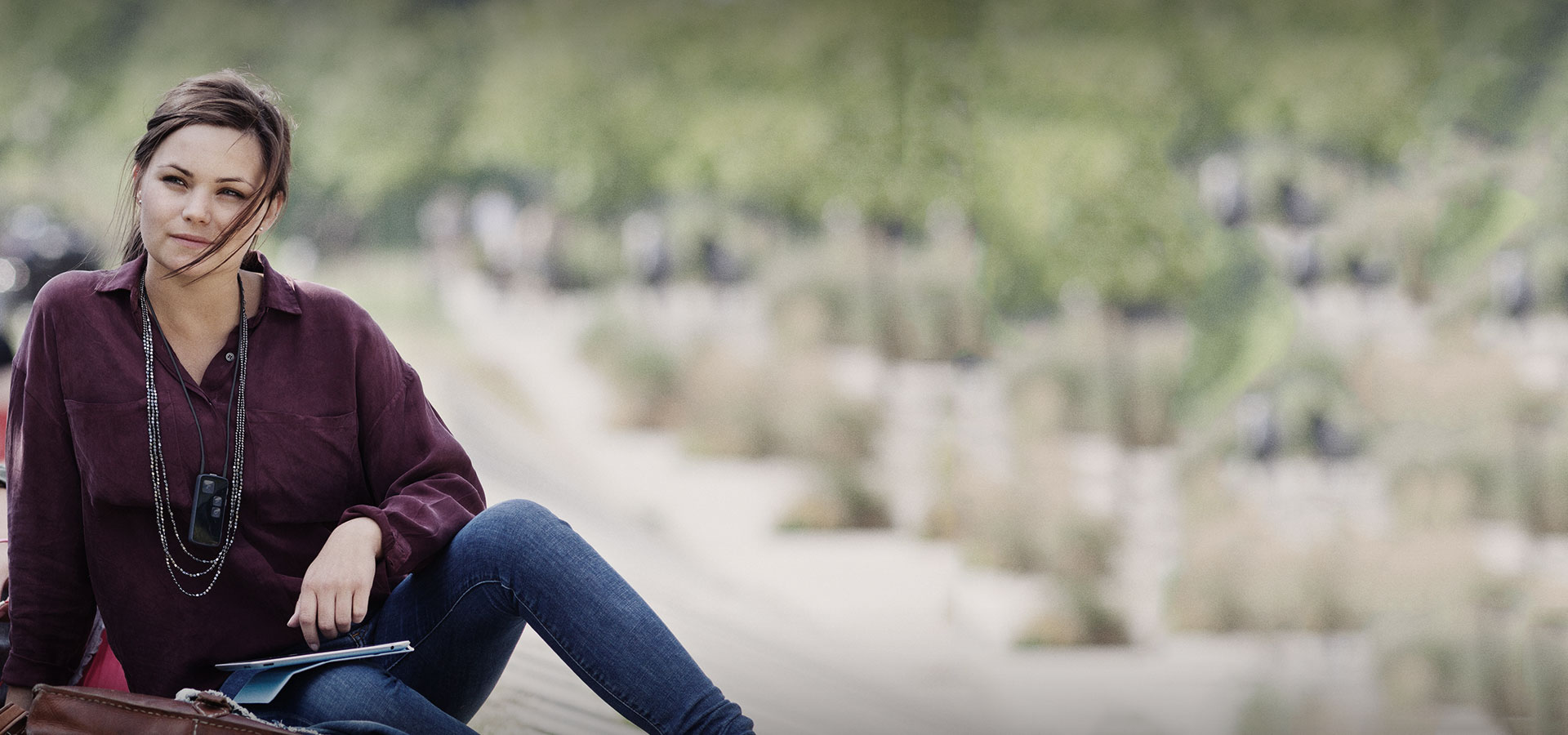 jeune fille adolescente avec chemise bodeaux et jean dans un parc
