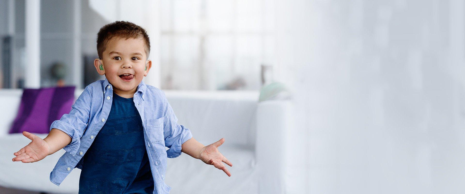 enfant joyeux bras ouverts avec appareils auditifs