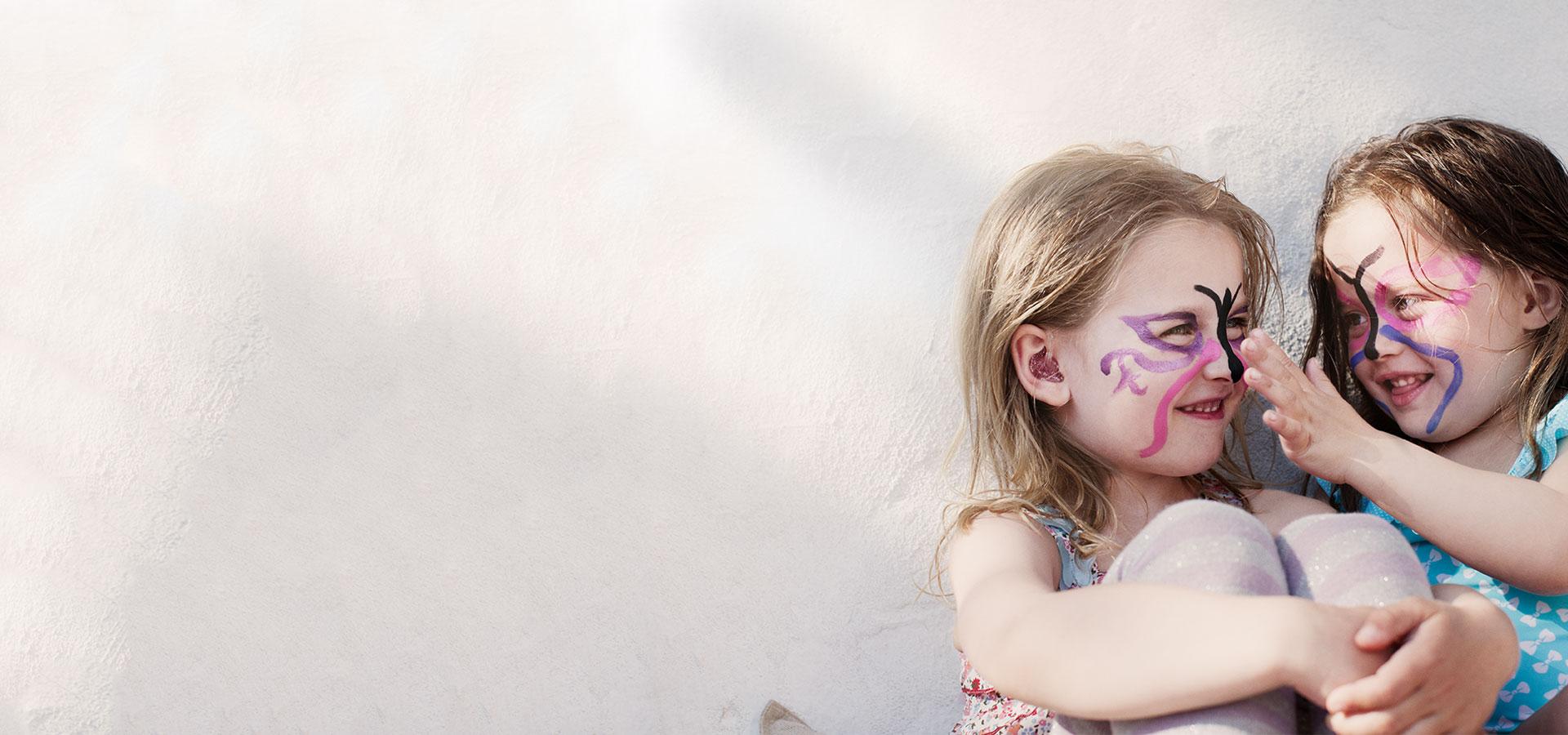 deux petits filles s'amusant avec du maquillage papillon sur le visage