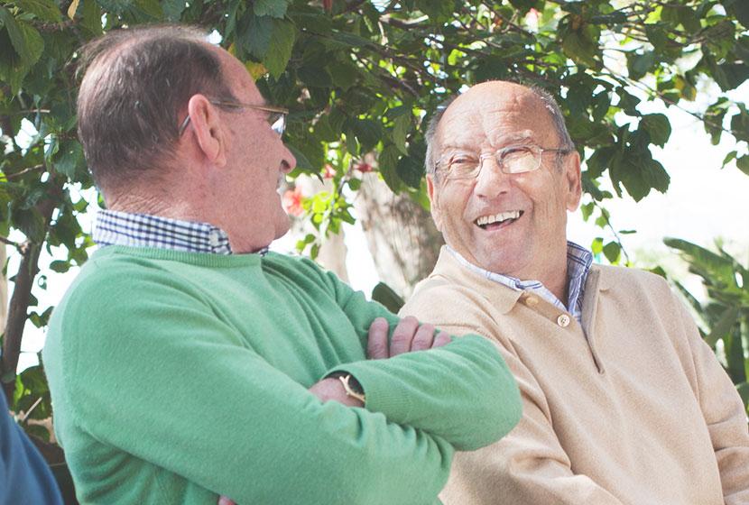 personnes âgées seniors parlant au soleil avec pull vert et beige