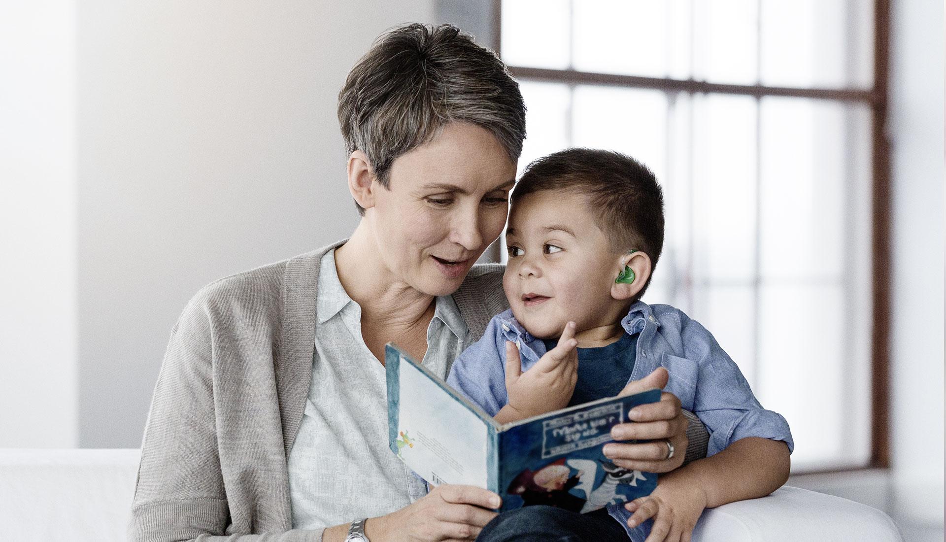 Femme et petit garçon portant un appareil auditif lisent un livre d'histoires