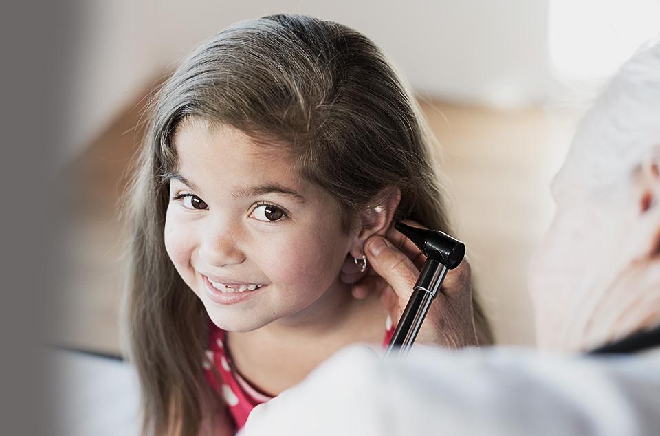 petit fille brune se faisant ausculter les oreilles par un médecin