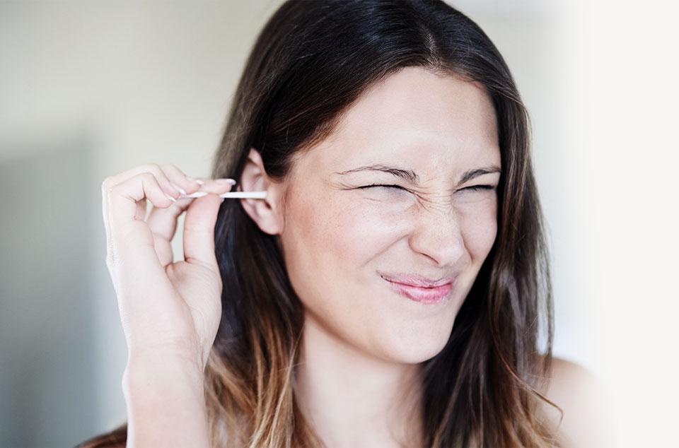 jeune femme se nettoyant les oreilles avec un coton tige en faisant la grimace