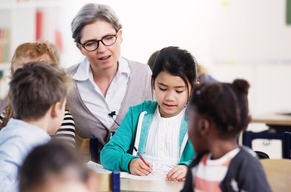 jeune professeur souriante parle à une petite fille dans la classe de cours