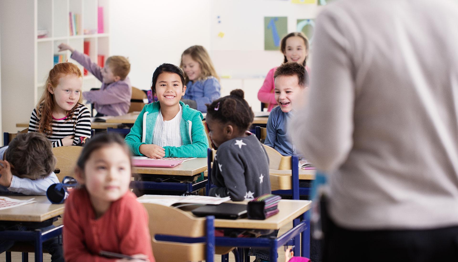 enfants en classe à l'école avec professeur de dos
