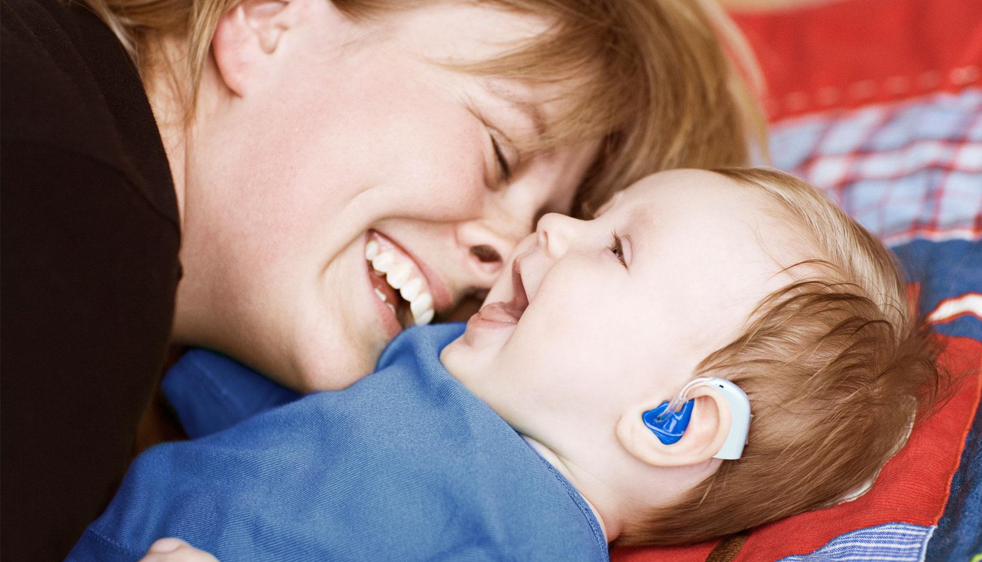 maman et son bébé avec un appareil auditif bleu riant aux éclats